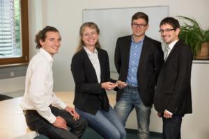Multiphoton Optics, Team: drei Männer, eine Chefin, sitzend strahlend auf einem Tisch oder stehen davor