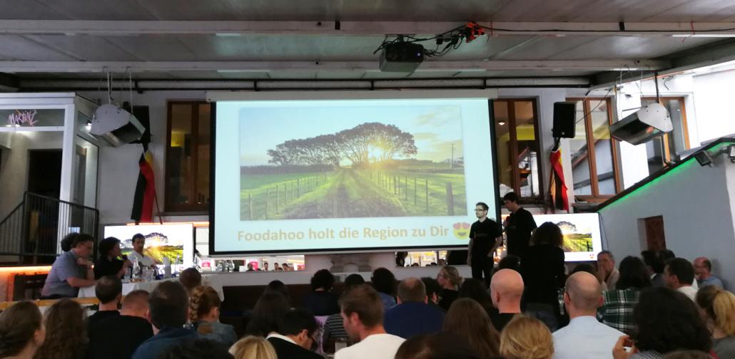 Foodahoo 3. Startup Preis Bühne, links Jury, zwei Mitglieder des Teams, Präsentation im Hintergrund