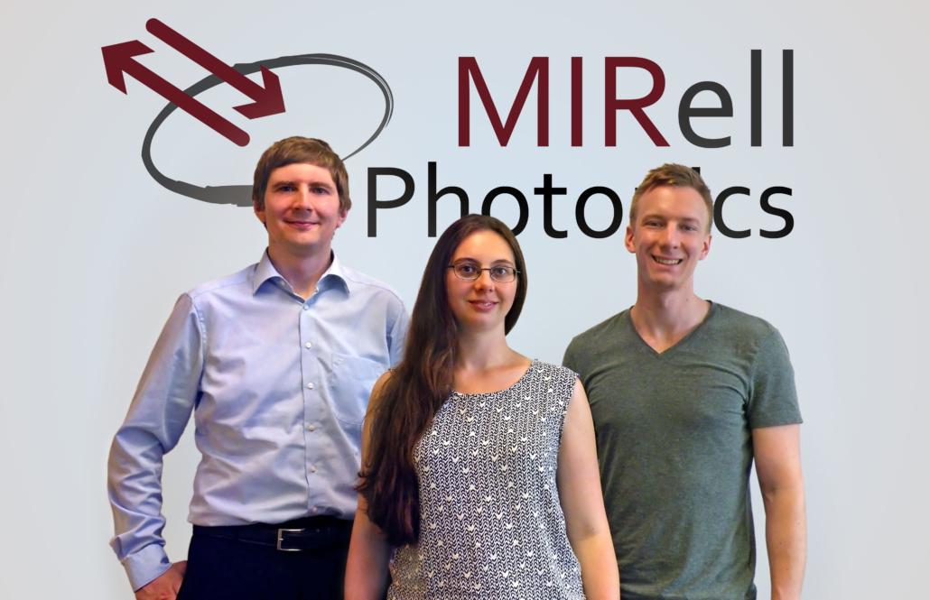 zwei Männer, eine Frau - das MIRell-Team vor ihrem Logo an der Wand