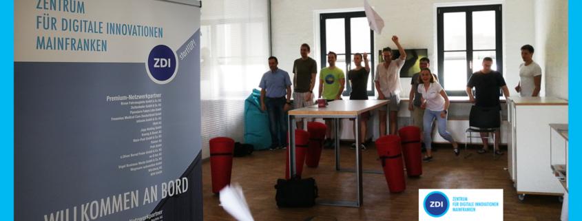 Menschen werfen Papierflieger, SChild mit Aufschrift ZDI Mainfranken