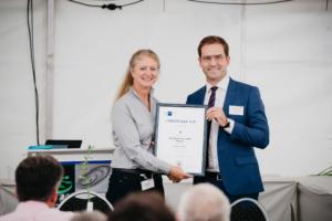 Houbertz erhält IHK-Ehrenurkunde von Deinhart, lächeln stolz in Kamera