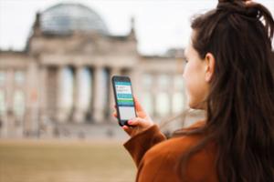 frau mit smartphone vor bundestag democy app offen